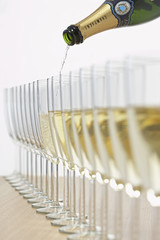 Bottle of champagne filling row of glasses, selective focus