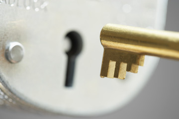 Golden key and padlock, close-up, selective focus