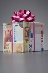Small gift wrapped in Euro notes with bow
