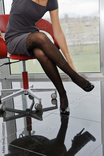 Professional woman's torso and legs sitting on office chair