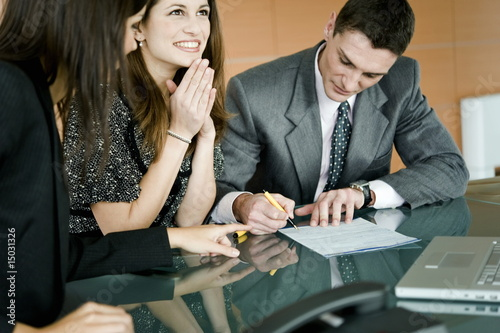 Young man signing document, professional woman pointing