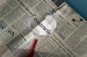 Magnifying glass over financial section of newspaper