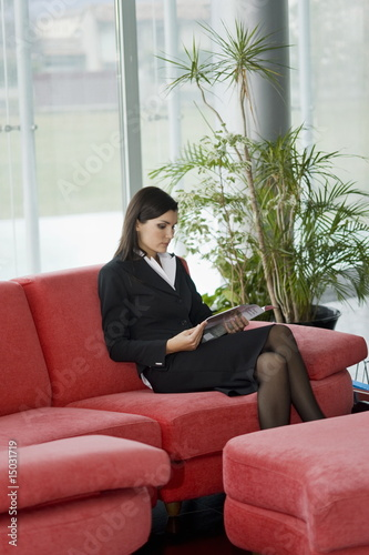 Professional woman sitting on couch reading