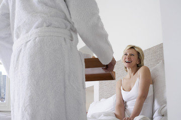 Man serving breakfast to woman in bed