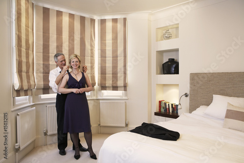 Middle-aged couple in bedroom, man helping woman with necklace