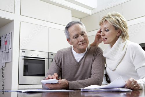 Middle-aged couple sitting in kitchen, counting bills using calculator