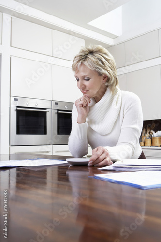 Middle-aged woman counting bills on calculator
