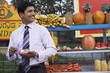 businessman standing in front of fruit stall