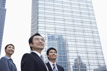 China, Hong Kong, three business people standing amongst skyscrapers, low angle view