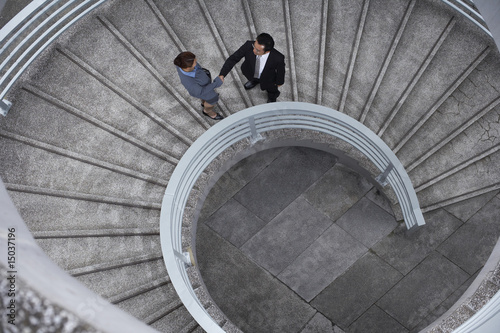 China, Hong, Kong, two business people shaking hands standing on spiral staircase, view from above