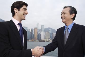 Two business men shaking hands, office buildings in background