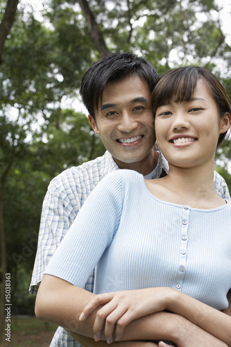 Mid adult couple embracing in park, portrait
