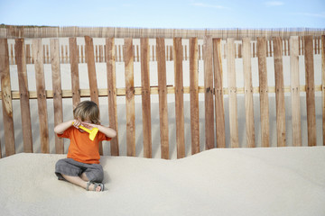 Boy 3-4 covering eyes, sitting against wooden fence on sand dune