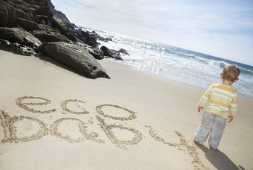Boy 1-2 standing by Eco Baby text written on beach