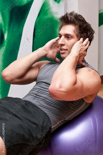 Smiling young man doing sit ups on a fitness ball
