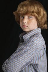 Boy 10-12 on black background, portrait