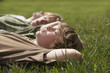 Three teenage brothers 13-17 lying down on grass, close up