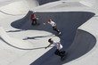 Three teenage boys 16-17 skateboarding at skate park, elevated view