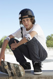Teenage boy 16-17 with skateboard at skateboard park, portrait