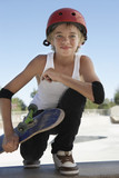 Teenage boy 13-15 with skateboard at skateboard park, portrait