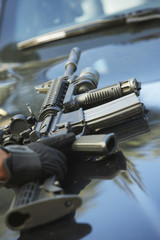 Close-up of police weapon on car bonnet
