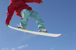 Teenage snowboarder jumping, cropped