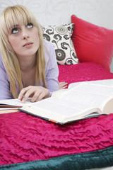 Teenage girl 16-17 lying on bed, looking up