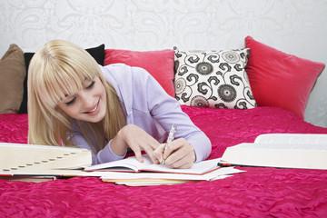 Teenage girl 16-17 lying on bed, writing