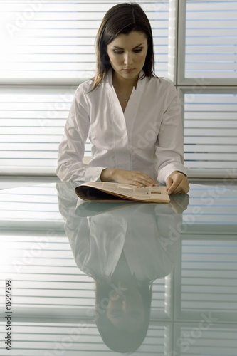 Professional woman reading newspaper at desk