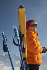 Woman smiling by ski and ski poles