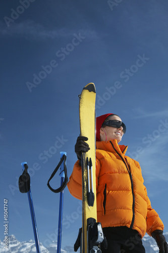 Woman smiling by ski and ski poles