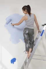 Woman standing on ladder painting wall