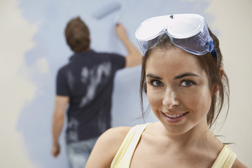 Couple painting wall, woman in foreground
