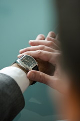 Businessman's hands checking the time on watch