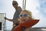 Girl 5-6 with mother on yacht, focus on foreground