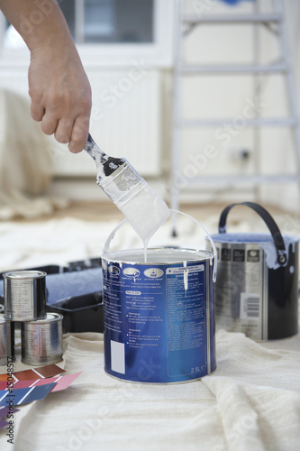 Man dipping paint brush into can, close up of hand