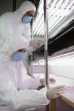 Workers in protective masks and suits in laboratory