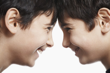Twin boys 13-15 head to head, laughing, close-up