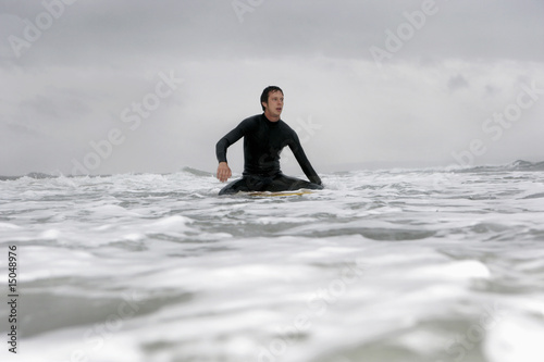 Young man on surfboard in ocean