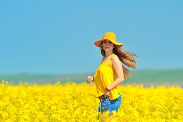 young woman on rape field in bloom