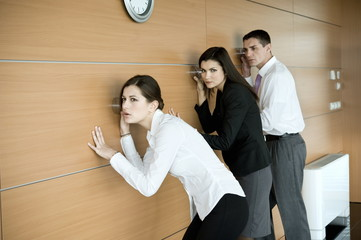 Office workers eavesdropping against wall