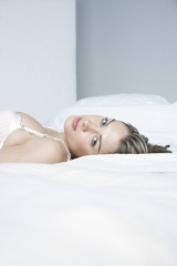 Young woman in underwear lying on bed, close-up