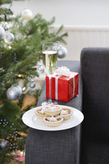 Glass of champagne and mince pies on armchair