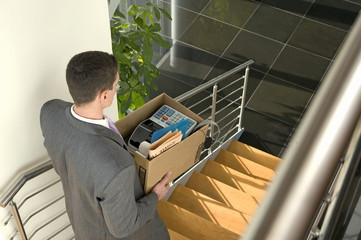 Businessman on office staircase with box of belongings