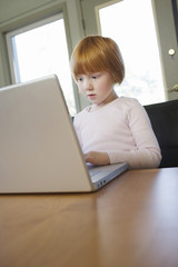 Young girl 5-6 using laptop, concentrated