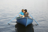 Young Couple Cuddling in Rowboat on Lake