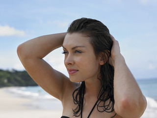 Young Woman at Beach with Hands in Hair