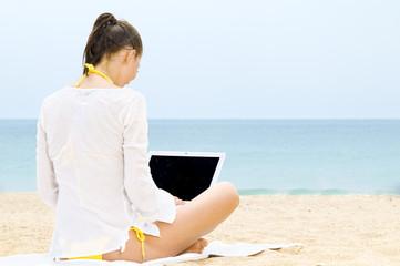 Frau sitzt mit Laptop am Strand