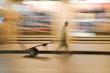 dubai uae a man wheels an empty cart through the streets of deira just after dark.