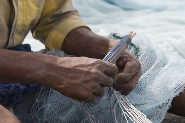 fujairah uae a local fisherman fixes holes and tangles in his net in fujairah.